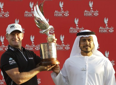 Jamie Donaldson from Wales, left, receives the trophy from Sheikh Sultan Bin Tahnoon Al Nahyan.