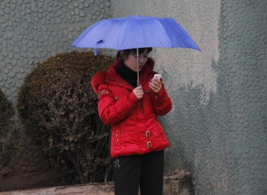 A North Korean woman uses a cellphone on a sidewalk in Pyongyang, North Korea (file photo).