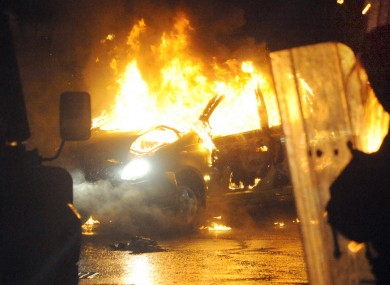 A burned out car during disturbances which erupted in east Belfast, with police coming under attack for a fourth night in a row.