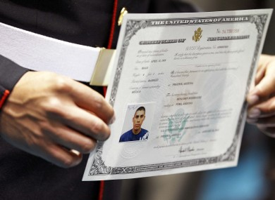 US Marine Lance Crpl. Benjamin Rodriguez displays his certficate of Citizenship after taking the oath of citizenship
