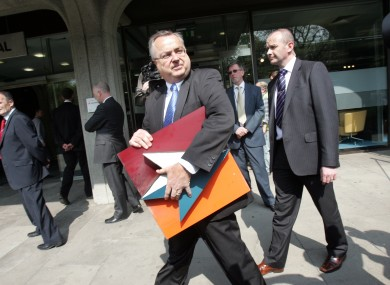 IBRC chief executive Mike Aynsley carries the old Anglo logo away from the bank's headquarters on St Stephen's Green.