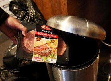 A packet of burgers is thrown into a bin.