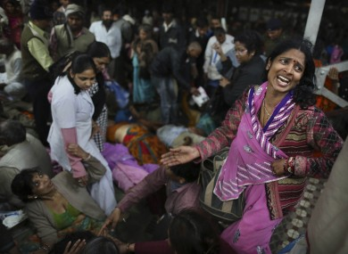 An Indian woman weeps as she and other family members mourn next to the body of a relative who was killed in the stampede.