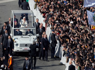 Pope Benedict XVI waves from his pope-mobile as he is driven through the crowd during his last general audience in St. Peter's Square.