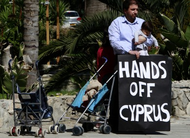 A protestor with his child hold a banner outside of parliament during a crucial meeting in capital Nicosia, Cyprus, yesterday.