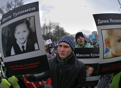 Demonstrators hold photos of adopted Russian children who died in the US during a giant rally in Moscow on 2 March
