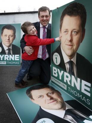Fianna Fáil Senator Thomas Byrne and Tomás (aged 4) inspect the Fianna Fáil by-election photos near Ashbourne yesterday evening.