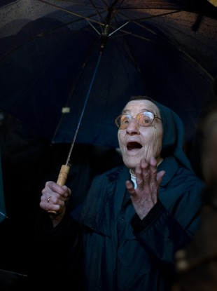 A nun reacts after seeing white smoke coming from the chimney on the Sistine Chapel on Wednesday