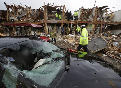 A smashed car sits in front of an apartment complex destroyed by an explosion at a fertiliser plant in West, Texas, as firefighters conduct a search and rescue mission.