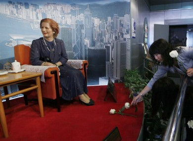 A staff member lays a flower in front of a wax statue of Margaret Thatcher at an exhibition center in Shenzhen, China, following Thatcher's de