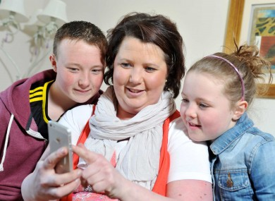 Karen McDermott, a mother of two from Clonakilty, who received a life saving heart transplant in August 2012 with her two children Nicola and Shane looking at the Donor Ecard Phone App.