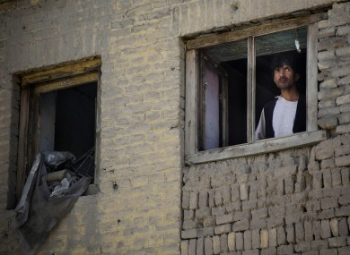 File: An Afghan man peers through a destroyed window of his house at the scene where a suicide car bomber attacked a NATO convoy in Kabul last week
