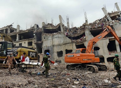 Rescuers carry a body retrieved from the rubble of the eight-story Rana Plaza building that collapsed in Savar, near Dhaka.