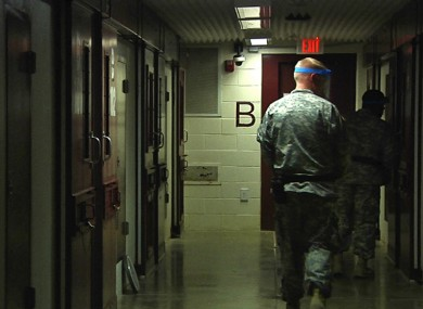 April 18, 2013 video frame grab reviewed by the U.S. military, soldiers walk past detainees' cells during early morning prayer at Guantanamo Bay Naval Base