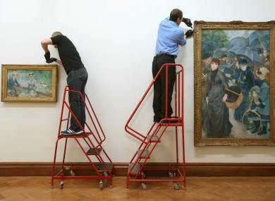 Art handlers hang Manet's Jour d'été and Renoir's Les Parapluies in the Hugh Lane Gallery in Dublin this week
