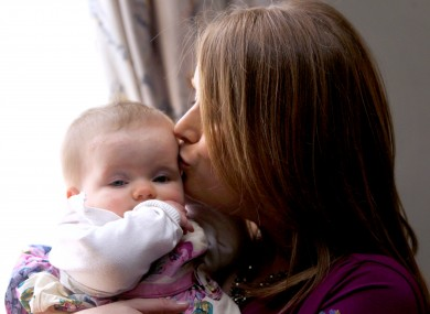 Julia Cummins, who had a kidney transplant, kisses her baby Laoise Nic Con Iomaire, in March