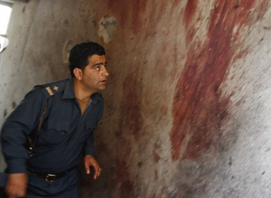 An Afghan policeman investigates the site after Taliban fighters attacked near Kabul airport this morning.