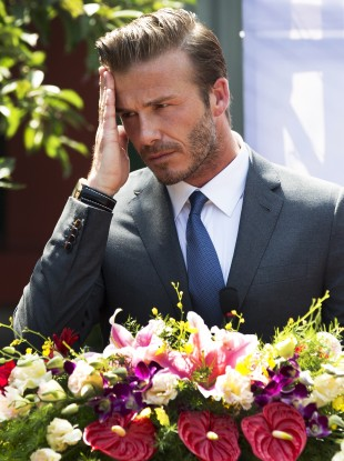 David Beckham wipes his sweat during his speech at a charity event at the Soong Ching Ling Residence in Beijing earlier this week.