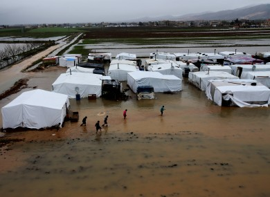 Syrian refugees make their way in flooded water at a temporary refugee camp, in the eastern Lebanese Town of Al-Faour