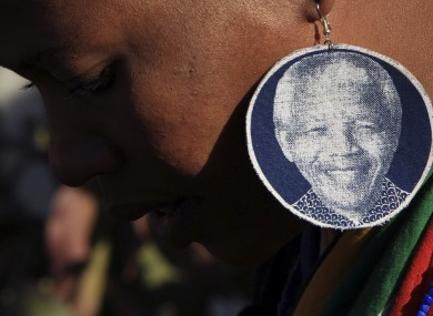 An unidentified woman wearing earrings bearing the image of former South African President Nelson Mandela, outside the Mediclinic Heart Hospital where he is being treated in Pretoria