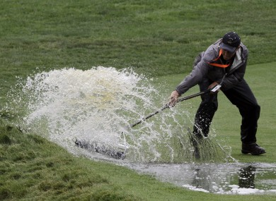 A course worker clears water from the 16th fairway