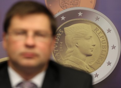 A reproduction of a Latvian euro coin is displayed, as Latvian Prime Minister Valdis Dombrovskis addresses the media on the adoption of the euro, at the European Council building in Brussels yesterday