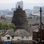 A massive bonfire dwarfs the houses in close to Lanark Way in West Belfast, Northern Ireland. (AP Photo/Peter Morrison)<span class=