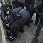 Police help a injured collegue after being attacked by Loyalists (Image: AP Photo/Peter Morrison)