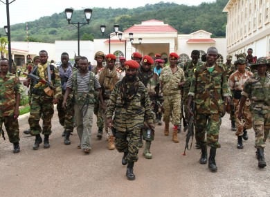 In this March 27, 2013 photo, rebel soldiers from the Seleka alliance walk in front of the Ledger Plaza Bangui hotel, in Bangui, Central African Republic.