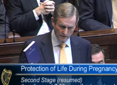 Taoiseach Enda Kenny with a copy of the constitution during the Dáil debate