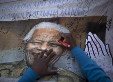 A South African woman, writes a get well message at a banner showing former South African President Nelson Mandela, placed at the entrance to the Mediclinic Heart Hospital.