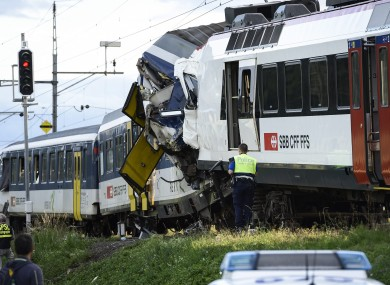 Police inspect the site where two passenger trains collided head-on in Granges-pres-Marnand, western Switzerland