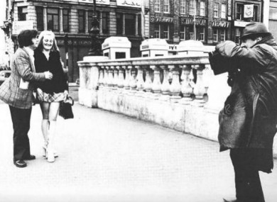 Arthur Fields takes a couple's photo on O'Connell bridge