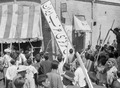 Demonstrators tear down the Iran Party's sign in Tehren on 19 August 1953