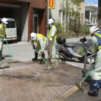City officials wearing masks clean the pavement(AP Photo/Kyodo News).
