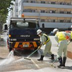 City officials clean the pavement covered by ash  after the eruption (AP Photo/Kyodo News).