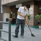 A store worker wearing a mask sweeps the pavement today (Image: Kyodo News/AP).