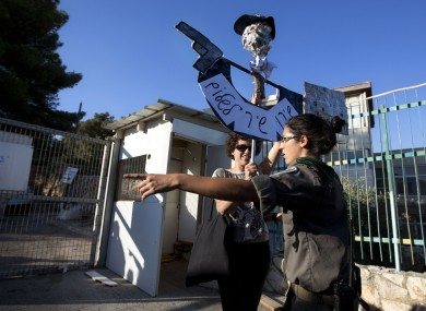 An Israeli border police officer argues with an Israeli left wing activist as she holds a sign to protests during a ceremony to mark the resumption of the construction of housing units in an east Jerusalem neighbourhood.