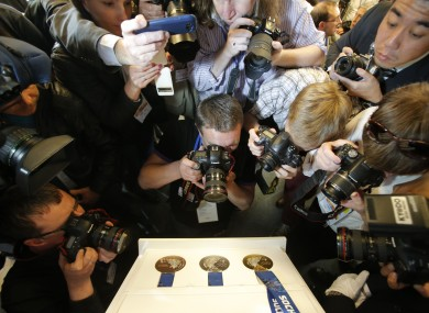 Photographers take images of the Sochi 2014 Olympics medals.