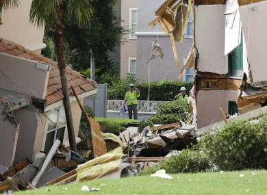 Inspectors look over damage to buildings caused by the sinkhole