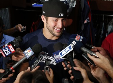 All smiles: New England Patriots quarterback Tim Tebow speaks to media in the locker room.