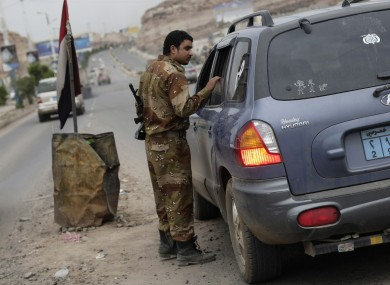 A Yemeni soldier inspects a car at a checkpoint on a street near the US embassy in Sanaa, Yemen