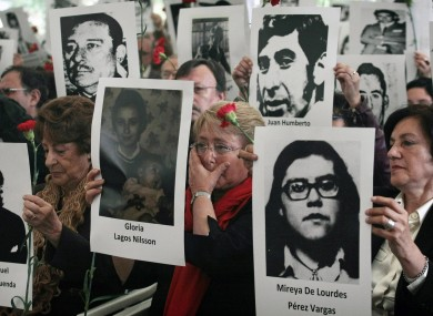 Chile's former President Michelle Bachelet, center, wipes a tear as she stands with her mother Angela Jeria, left, and Margarita Romero, president of the Villa Grimaldi organization, right, all holding photographs of victims of the dictatorship of Gen. Augusto Pinochet