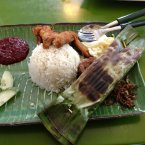 Widely considered the unofficial national dish of Malaysia, nasi lemak consists of rice cooked in coconut milk and pandan leaf. It was suggested by Quora user Shixian T.  It's traditionally served wrapped in banana leaves and is often accompanied by sambal chili, ikan bilis (anchovies), peanuts, and boiled egg.  Many people also believe it cures hangovers.<span class=