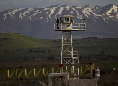 A U.N. peacekeeper from the UNDOF force stands guard on a watch tower at the Quneitra Crossing in the Golan Heights
