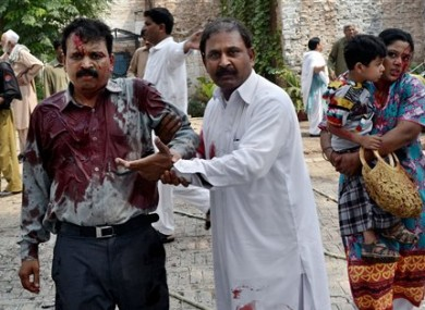 A Pakistani man helps an injured victim of a suicide attack at a church in Peshawar, Pakistan.