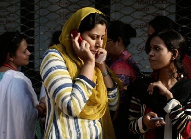 A Pakistani woman speaks on her mobile phone after rushing out of her apartment.