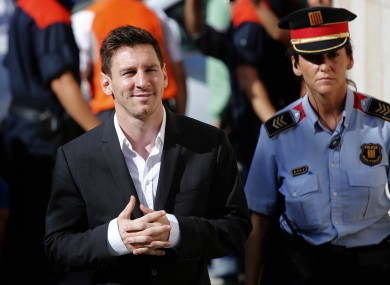 Barcelona star Lionel Messi, left, arrives at a court to answer questions in a tax fraud case.