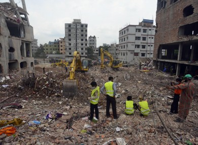 Workers examine the site of the collapsed garment factory in Savar near Dhaka.