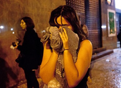 A woman covers from tear gas fired by police near the Cinelandia square in Rio de Janeiro